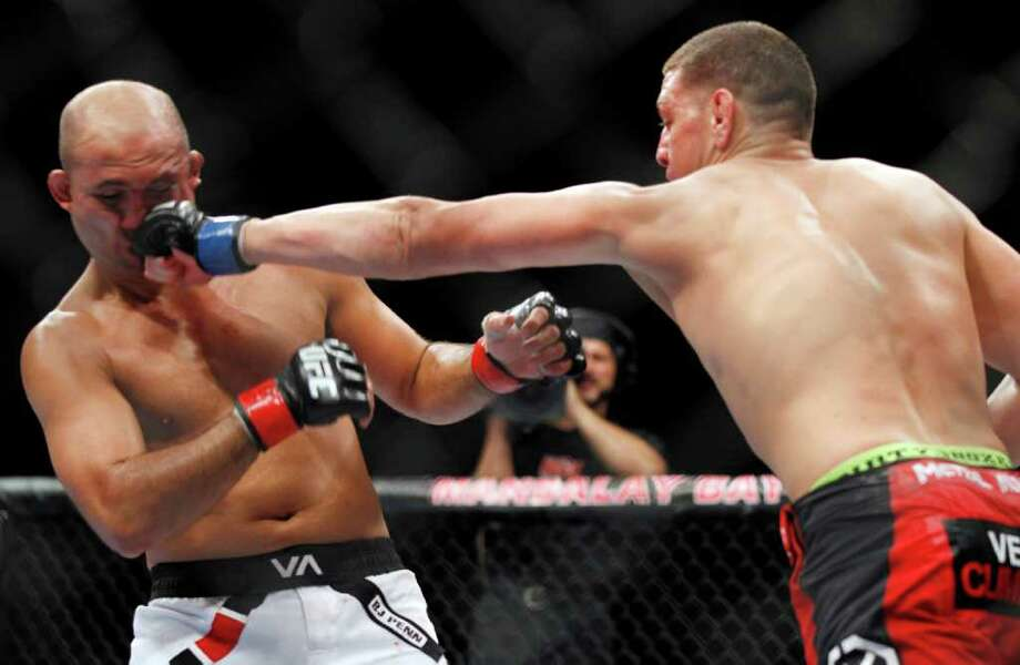 Nick Diaz, right, punches BJ Penn during a mixed martial arts welterweight bout, Saturday, Oct. 29, 2011, in Las Vegas. Diaz won by unanimous decision. (AP Photo/Isaac Brekken) Photo: Isaac Brekken, Associated Press / FR159466 AP