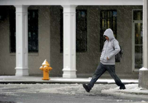 Taking a wide step over a puddle, Gabriel Perez, of Stratford, makes his way across Broad Street, during a snow storm in Milford, Conn. on Saturday October 29, 2011. Photo: Christian Abraham / Connecticut Post