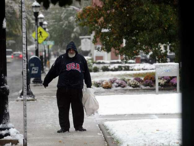 Jerry Landino, of West Haven, makes his way along Broad Street to the bus stop, during a snow storm in Milford, Conn. on Saturday October 29, 2011. Photo: Christian Abraham / Connecticut Post