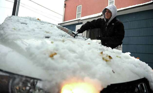 Christina Engengro cleans off her car at her home on Depot Street during a snow storm in Milford, Conn. on Saturday October 29, 2011. Photo: Christian Abraham / Connecticut Post