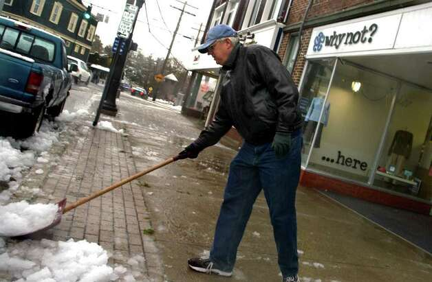 Steve Rathbun, co-owner of Why Not? clothing store cleans his sidewalk along Broad Street, during a snow storm in Milford, Conn. on Saturday October 29, 2011. Photo: Christian Abraham / Connecticut Post