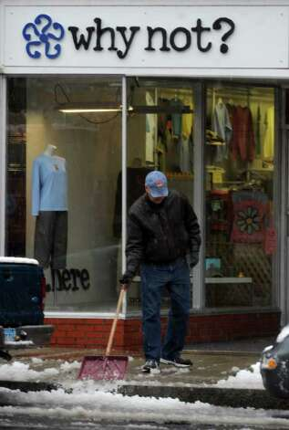 Scenes from Saturday's nor'easter as it goes through Milford, Conn. on October 29, 2011. Steve Rathbun, co-owner of Why Not? clothing store cleans his sidewalk along Broad Street. Photo: Christian Abraham / Connecticut Post