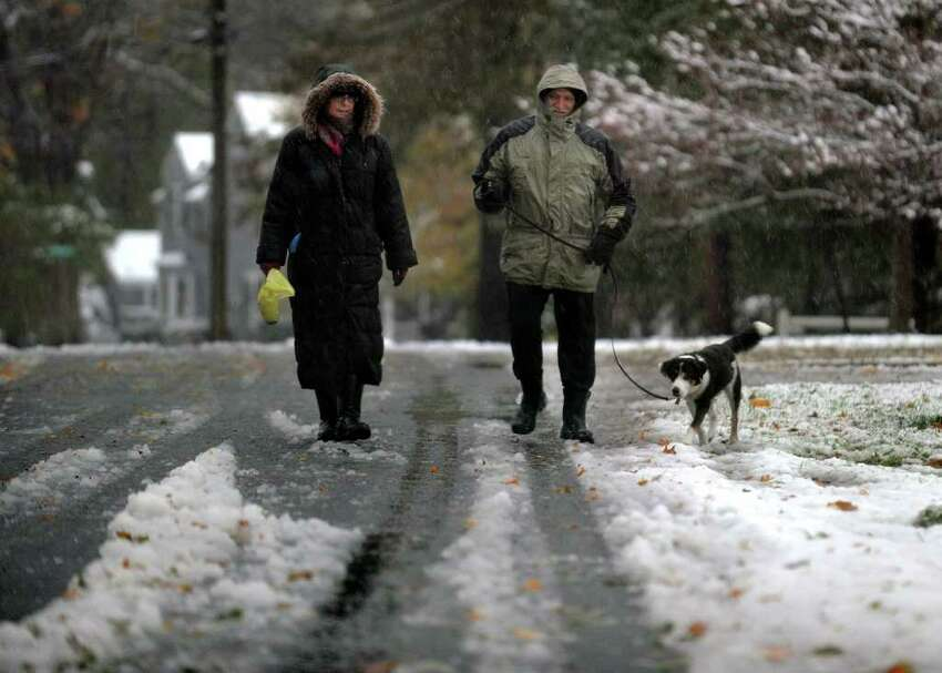 Holly and Carl Franquet walk along Old Mill Road with their dog Bree, during a snow storm in Fairfield, Conn. on Saturday October 29, 2011.