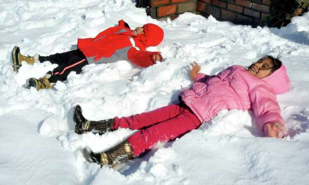 Not everyone was troubled by the snow. Marbin Madvid, 5, left, and his sister, Sindi, 6, make snow angels in Danbury Sunday, Oct. 30, 2011. Photo: Michael Duffy