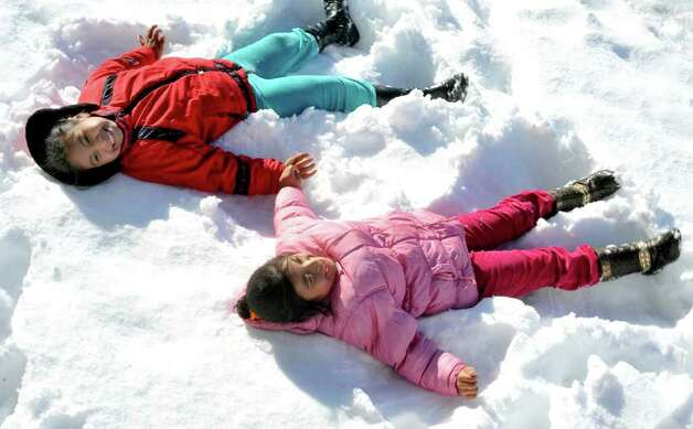 Dolores Madvid, 8, left, and her sister, Sindi, 6, make snow angels in Danbury Sunday, Oct. 30, 2011. Photo: Michael Duffy