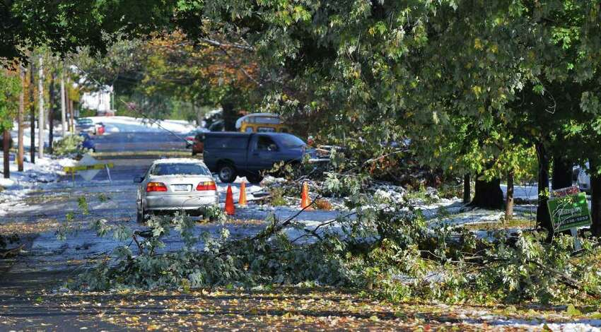 Vehicles avoid a downed utility line and fallen trees on Elm Street in Saugerties, NY, following a surprise fall snowstorm the previous night, on Sunday Oct. 30, 2011. (Philip Kamrass / Times Union )