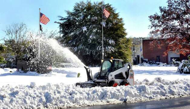 Snow removal is happening early in front of the War Memorial in Danbury Sunday, Oct. 30, 2011. Photo: Michael Duffy