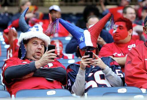 Texans fans on their phones before the start of an NFL football game at Reliant Stadium, Oct. 30, 2011. Photo: Karen Warren, Houston Chronicle / © 2011 Houston Chronicle