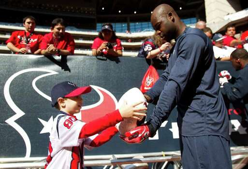 Houston Texans cornerback Johnathan Joseph autographs a football for Alexander Phillips, 5, before an NFL football game against the Jacksonville Jaguars at Reliant Stadium on Sunday, Oct. 30, 2011, in Houston. Photo: Brett Coomer, Houston Chronicle / © 2011  Houston Chronicle