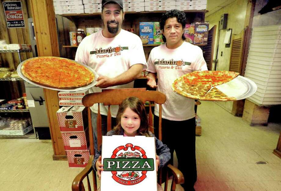 Tom DeMatteis stands in his Danbury business, Martino's Pizza, accompanied by his daughter, Liberty DeMatteis, 5, and Marcos Aguilar, Saturday, Oct. 29, 2011. Photo: Michael Duffy / The News-Times
