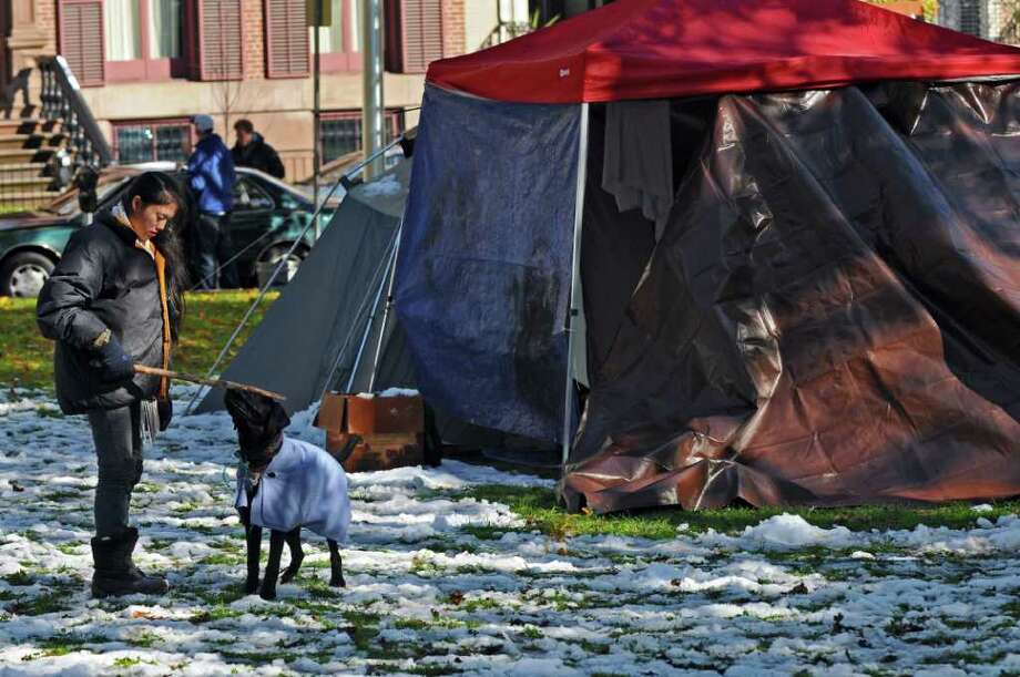Soojee Eckhardt-Rigberg of Albany plays with her dog Obi near her tent (not shown) on snow remaining from the previous night's surprise snowstorm, at the Occupy Albany encampment in Academy Park on Sunday Oct. 30, 2011 in Albany, NY. She has been camped there since last Friday, the first day of the protest. (Philip Kamrass / Times Union ) Photo: Philip Kamrass / 00015200A