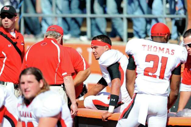 Lamar Cardinals quarterback Andre Bevil, center,  leaves the game late in the first quarter after suffering an ankle injury against Sam Houston State  at Bowers Stadium in Huntsville on Saturday, October 29, 2011.  Valentino Mauricio/The Enterprise Photo: Valentino Mauricio