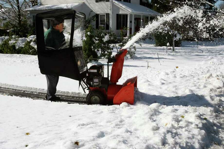 Benny Conte, of Monroe, clears his driveway Sunday morning, October 30, 2011. All of Saturday's nor'easter left Monroe residents  without power. Photo: B.K. Angeletti / Connecticut Post