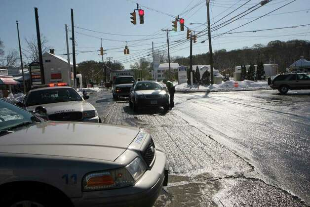 Police officers direct traffic away from fallen trees and downed wires on Main Street in Monroe on  Sunday, October 30, 2011. Saturday's nor'easter left Monroe residents without power. Photo: B.K. Angeletti / Connecticut Post