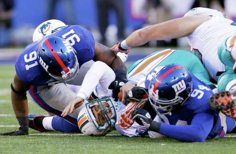 Giants 20, Dolphins 17. Miami Dolphins quarterback Matt Moore, center, is sacked by New York Giants' Justin Tuck (91) and Mathias Kiwanuka (94) during the fourth quarter. Photo: Julio Cortez, Associated Press / AP