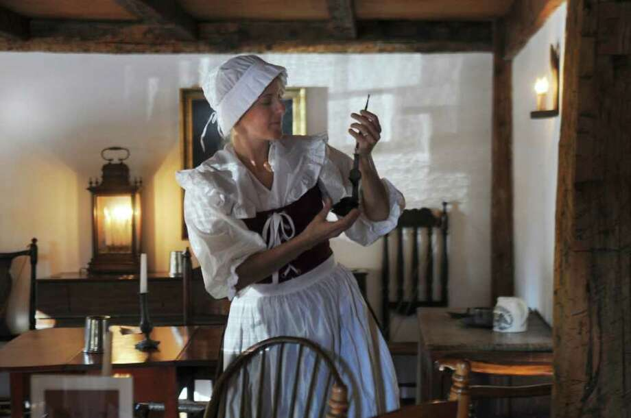 """Gayle Hagegard holds an antique ladle Sunday, Oct. 30, 2011, at the Putnam Hill chapter of the Daughters of the American Revolution's """"Headless Horseman at the Haunted Cottage,"""" at the Putnam Cottage Knapp Tavern Museum. Photo: Helen Neafsey / Greenwich Time"""