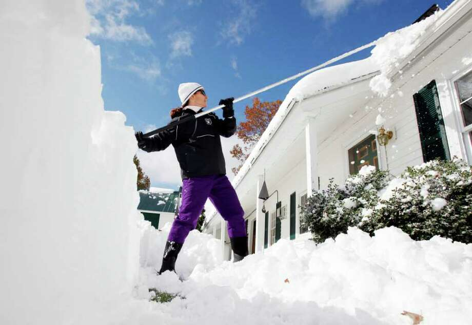 Sarah Arel clears snow from her roof in Ashburnham, Mass., Sunday, Oct. 30, 2011. Millions of people in the U.S. Northeast were without power as an unseasonably early storm dumped heavy, wet snow over the weekend on a region more used to gaping at leaves in October than shoveling snow. Photo: Michael Dwyer, Associated Press / AP