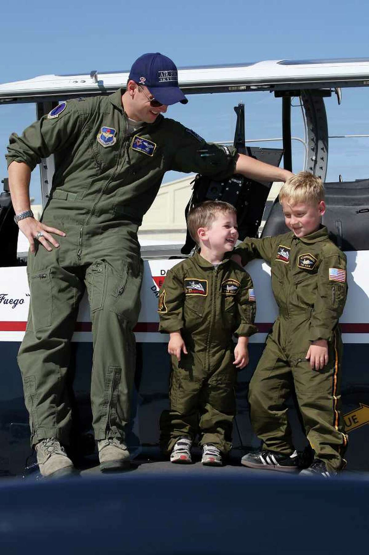 METRO - In their Halloween costumes, brothers Jay, 4, center, and Ian Campbell, 4, of Schertz, pose with Lt. John Harvey by a T-6A Texan II during the last day of the Randolph Air Show, Sunday, Oct. 30, 2011. The show featured the U.S. Navy Blue Angels as its finale. The Texan is part of the 359th Flying Training Squadron at the base. Campbell was dress in his Halloween costume. JERRY LARA/glara@express-news.net