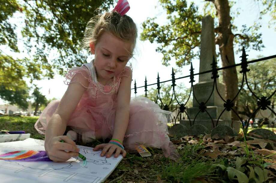 Lillian Dowe, 5, finds a quiet place to color Sunday during a visit to Founders Memorial Park Cemetery, which was founded in the 19th century. Photo: Nathan Lindstrom / ©2011 Nathan Lindstrom