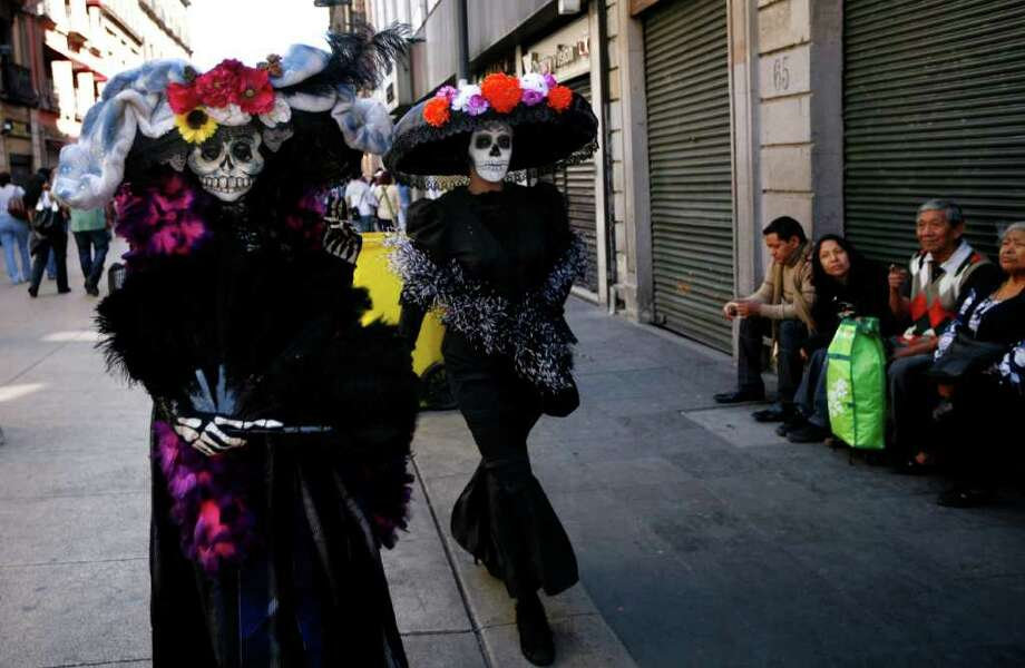 "Women dressed as traditional Mexican ""Catrinas"" walk through downtown for Day of the Dead celebrations in Mexico City, Sunday Oct. 30, 2011. Photo: AP"