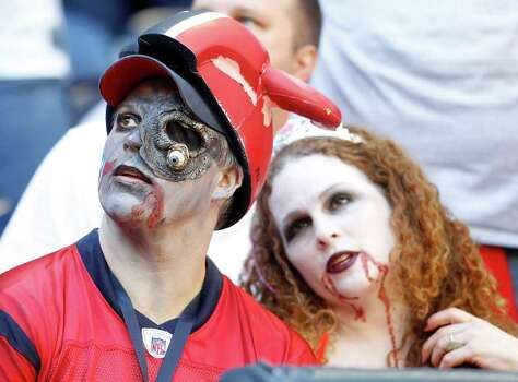 Donnie and Amy Eason, of League City, wear their Halloween costumes as they watch the game in the fourth quarter of an NFL football game at Reliant Stadium, Oct. 30, 2011.  Houston won the game 24-14. Photo: Karen Warren, Houston Chronicle / © 2011 Houston Chronicle
