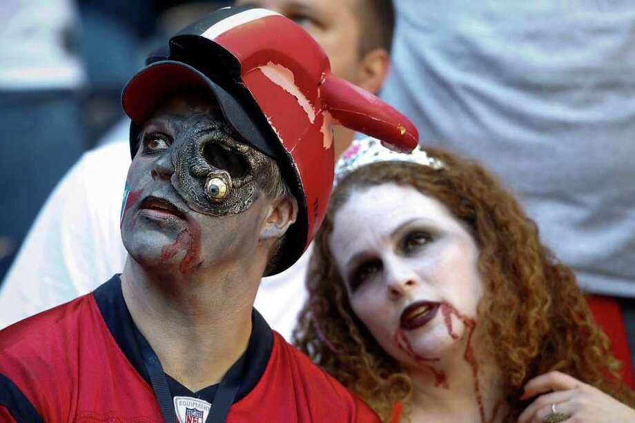Donnie and Amy Eason of League City wears Halloween costumes as they watch the game in the fourth quarter. Photo: Karen Warren, Houston Chronicle / © 2011 Houston Chronicle
