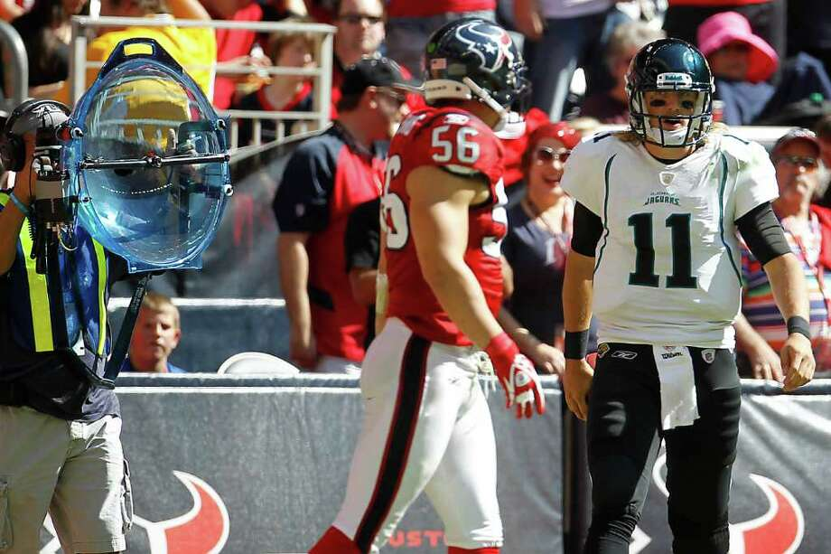 Jacksonville Jaguars quarterback Blaine Gabbert (11) has words with Houston Texans inside linebacker Brian Cushing (56) in proximity to a television broadcast microphone in the third quarter. Photo: Karen Warren, Houston Chronicle / © 2011 Houston Chronicle