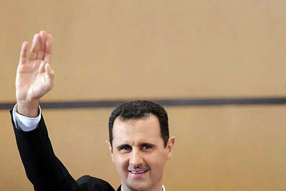 """FILE - In this Monday, June 20, 2011 file photo released by the Syrian official news agency SANA, Syria's President, Bashar Assad waves to the audience after he delivers a speech in Damascus, Syria. Syrian President Bashar Assad warned against Western intervention in his country's 7-month-old uprising, saying such action would trigger an """"earthquake"""" that """"would burn the whole region.""""  (AP Photo/SANA, File) EDITORIAL USE ONLY"""