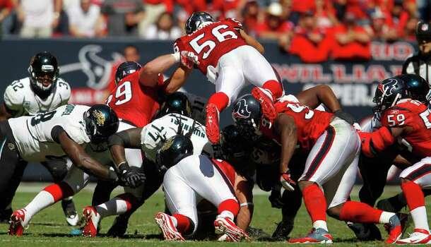 Houston Texans inside linebacker Brian Cushing (56) jumps over the pack during the second quarter. Photo: Karen Warren, Houston Chronicle / © 2011 Houston Chronicle
