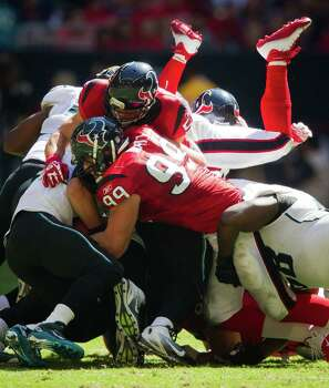 Houston Texans inside linebacker Brian Cushing (56) and defensive end J.J. Watt (99) make a short yardage stop on Jacksonville Jaguars quarterback Blaine Gabbert (11) during the second quarter. Photo: Smiley N. Pool, Houston Chronicle / © 2011  Houston Chronicle