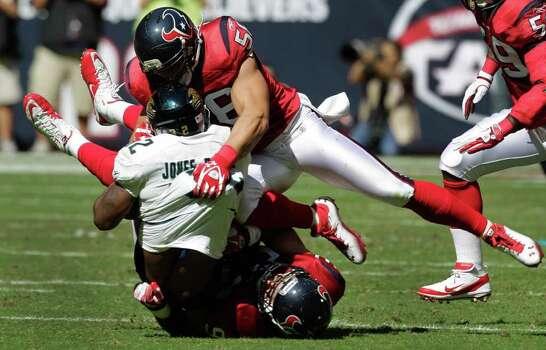 Houston Texans inside linebacker Brian Cushing (56) and defensive end J.J. Watt (99) stop Jacksonville Jaguars running back Maurice Jones-Drew (32) during the second quarter. Photo: Brett Coomer, Houston Chronicle / © 2011  Houston Chronicle