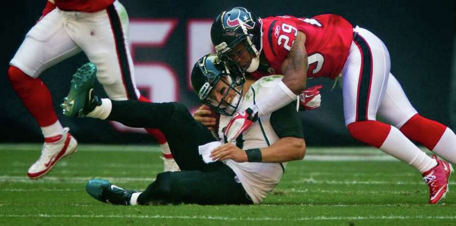 Jacksonville Jaguars quarterback Blaine Gabbert (11) is slammed to the turf by Houston Texans strong safety Glover Quin (29) during the first quarter. Gabbert was shaken up on the play and left the game. Photo: Smiley N. Pool, Houston Chronicle / © 2011  Houston Chronicle