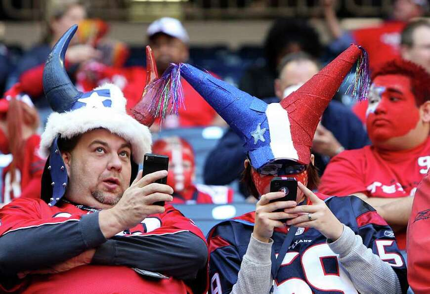 Texans fans check their phones before the start of the game.