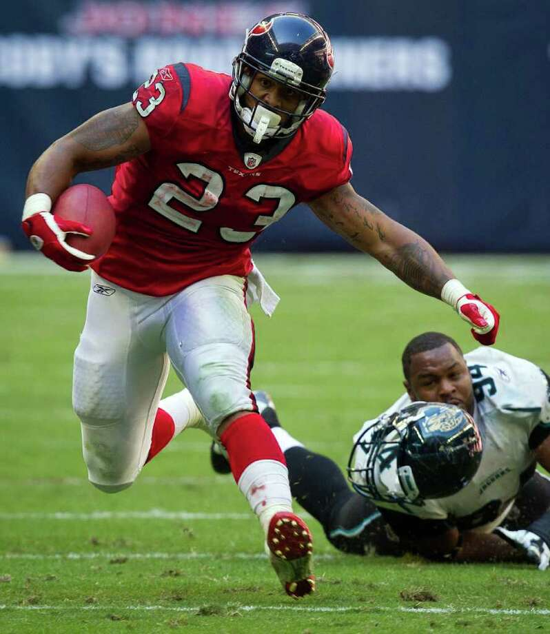 OFF AND RUNNING: Texans back Arian Foster (23), who had 112 yards on 33 carries, jukes Jacksonville's Jeremy Mincey out of his helmet. Photo: Smiley N. Pool / © 2011  Houston Chronicle