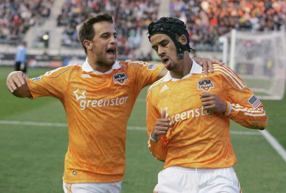 CHRIS GARDNER : GETTY IMAGES LEG UP: Bobby Boswell, left, congratulates Calen Carr for scoring the goal that put the Dynamo in the driver's seat in the two-game conference semifinal series with the Union. Photo: Chris Gardner / 2011 Getty Images