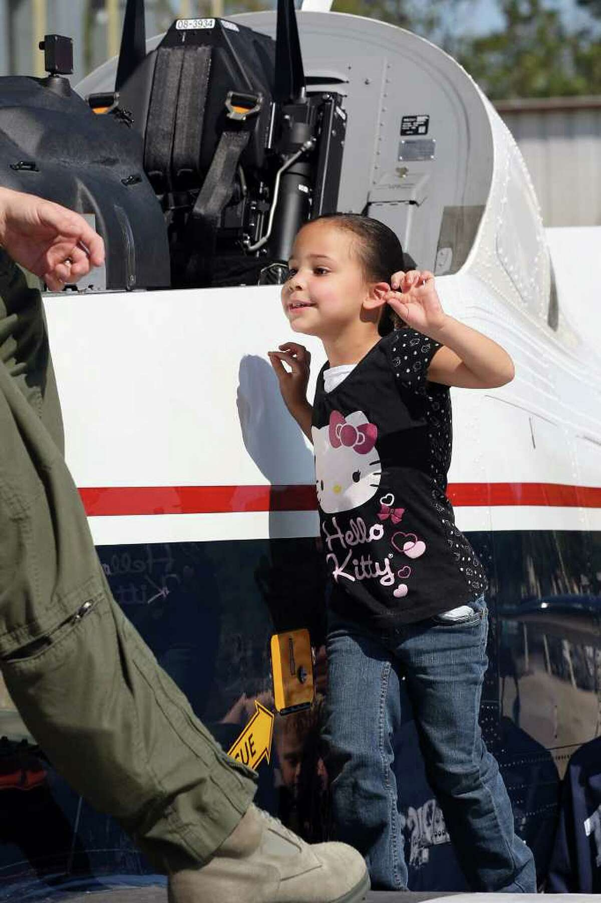Kathrena Morgan, 4, of Virginia Beach, makes it to the wing of a T-6A Texan II during the last day of the Randolph Air Show, Sunday, Oct. 30, 2011. The show featured the U.S. Navy Blue Angels as its finale. The Texan is part of the 359th Flying Training Squadron at the base. Campbell was dress in his Halloween costume.