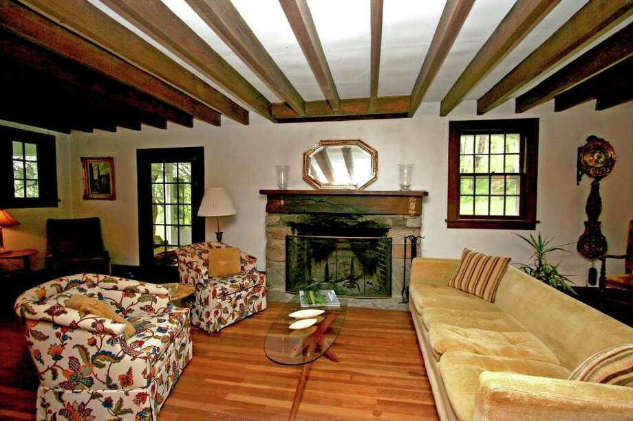 The vintage colonial house designed by Minerva Parker Nichols, one of the country's first female architects, features exposed wood beams throughout, including in the living room with wide stone fireplace. Photo: Contributed Photo