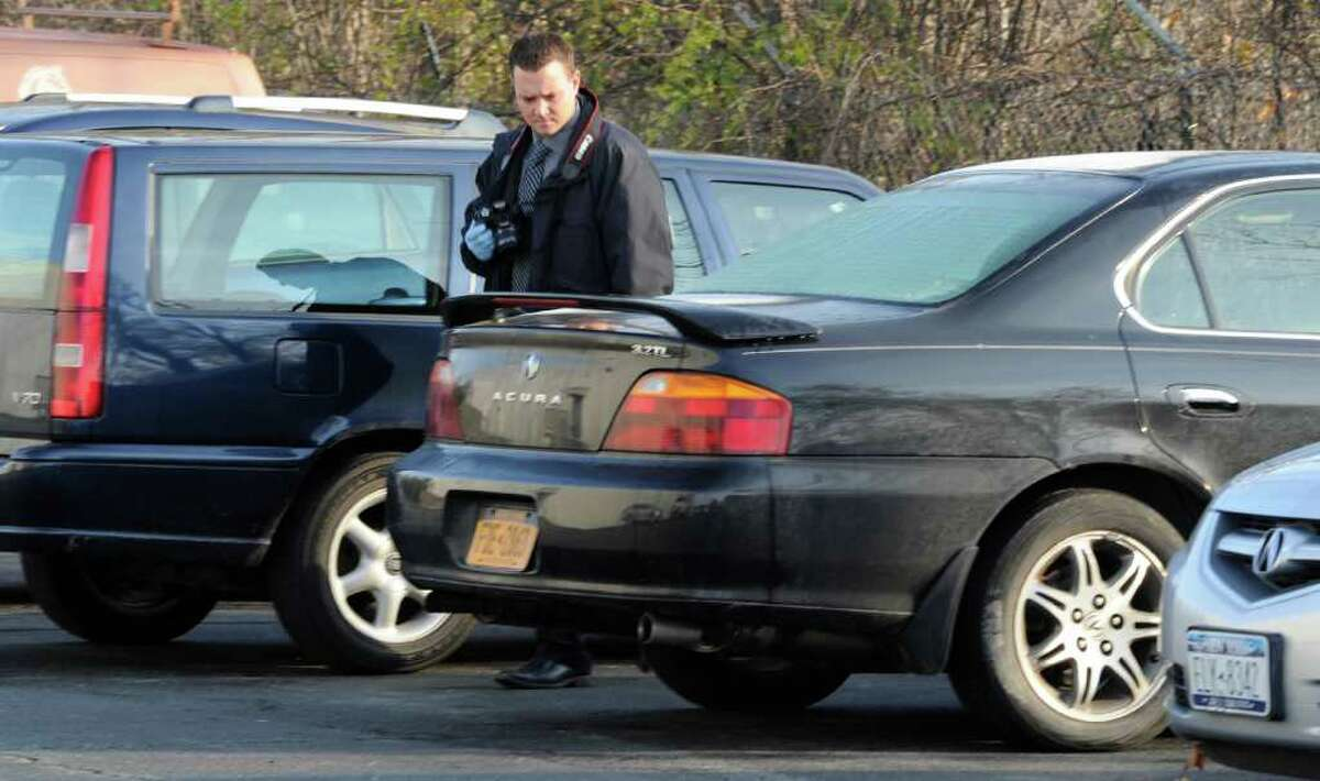 A Colonie Police forensics investigator looks over a car that was subsequently towed from Gold's Gym in Latham, N.Y., after a man died after a struggle with Colonie Police at the gym early on October 31, 2011. (Skip Dickstein / Times Union)