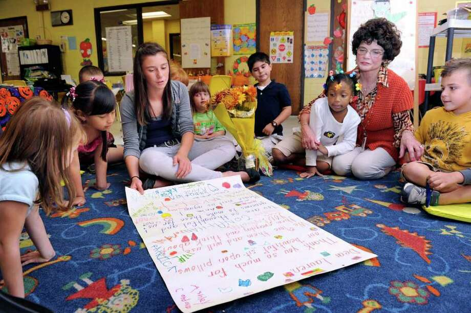 Danbury Girl Scout Lauren Guiry, 13, center of Danbury, visits with Maureen McGarrigal's kindergarten class at King Street Primary School. McGarrigal, right, was Lauren's kindergarten teacher. As part of a Girl Scout project, Lauren made cushions for the kindegartners to sit on during their morning circle time. In photo, she reads the oversized thank you card the kids made for her. Photo: Carol Kaliff