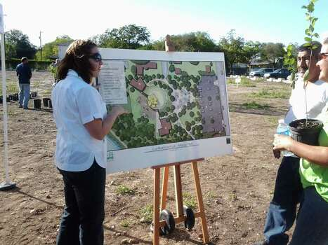 Karen Kimball with the San Antonio River Foundation shows visitors a conceptual scheme of the envisioned Confluence Park during an Oct. 20 tree giveaway at the park near Mission Concepcion. The public park will be a key site along the San Antonio River's Mission Reach, supporting public recreational activities and ecological education efforts. Photo: Courtesy Photo