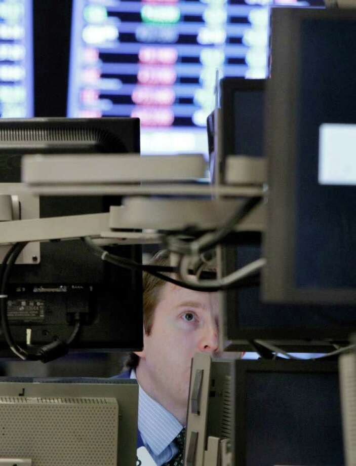Specialist Peter Elkin watches his monitors as he works on the floor of the New York Stock Exchange Monday, Oct. 31, 2011. (AP Photo/Richard Drew) Photo: Richard Drew / AP