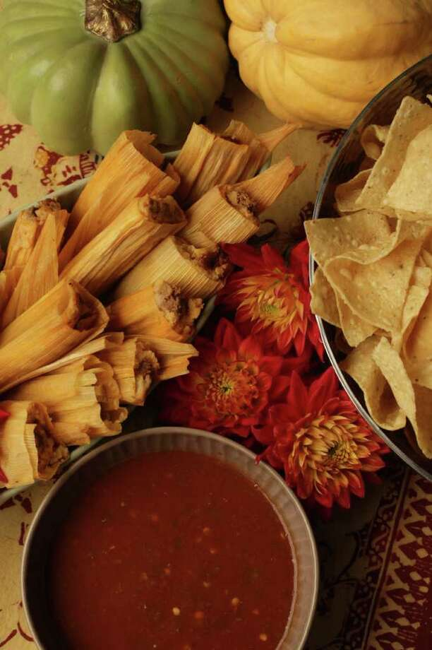 Nick de la Torre : Houston Chronicle SIMPLE FEAST: Molina's tamales, chips and salsa. Oval aqua serving bowl, $25, small brown bowl, $12, and table runner, $50, Texas Tuscan. Hammered silver bowl, $24, Surroundings. Photo: Nick De La Torre / © 2011  Houston Chronicle