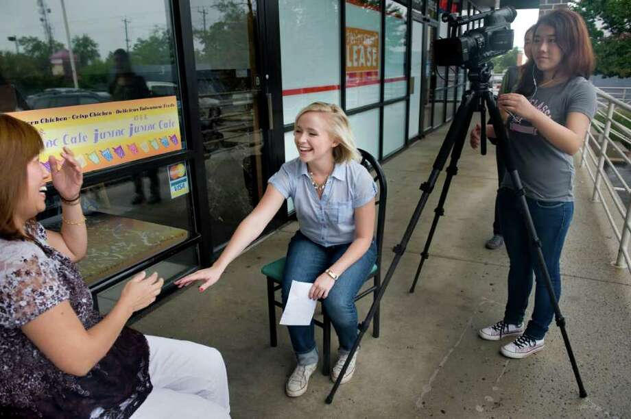 Meiyu host Jessica Beinecke, 24, center, with Yuyang Ren behind the camera, interviews Maryland shop owner Cathy Yen for a segment on her Voice of America online show that translates American slang and culture for her Chinese audience. Photo: NIKKI KAHN, WASHINGTON POST / The Washington Post