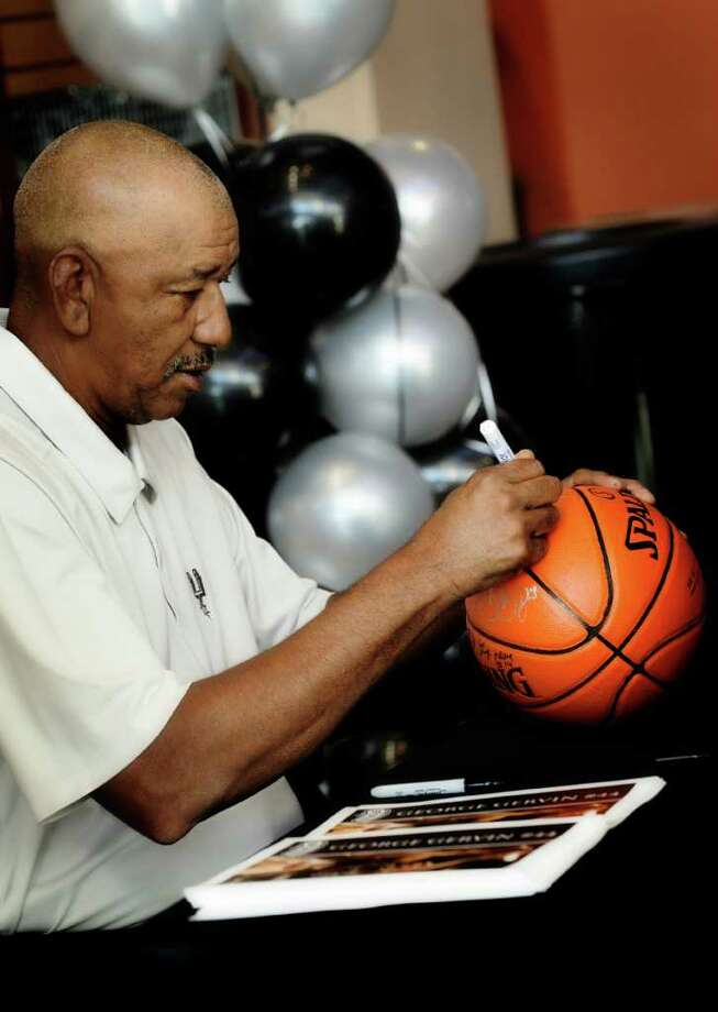 George Gervin signs a basketball for a fan during the Spurs Family Fall Fiesta at the AT&T Center last month.