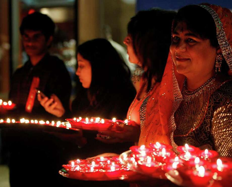 Participants hold plates of lit diyas, or candles, during Diwali, an Indian festival also known as the festival of lights. Photo: MICHAEL MILLER, STAFF / mmiller@express-news.net