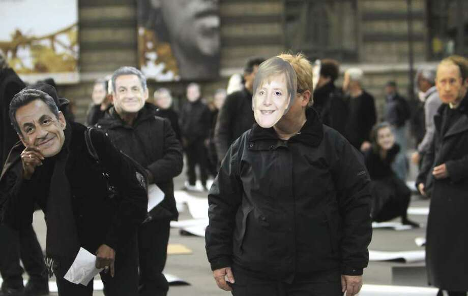 French activists wear masks depicting leaders of the G20  French President Nicolas Sarkozy,left, German Chancellor Angela Merkel, in Paris, France, Thursday, Oct. 27, 2011. Protesters are demonstrating against a gathering of the world leaders in the southern French city of Cannes for the G20 summit next week. Photo: Jacques Brinon, AP / AP