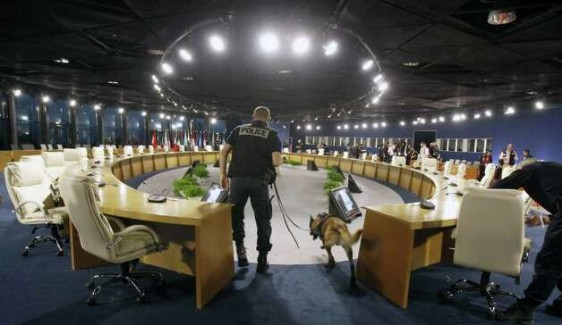A police officer and a dog conduct a security sweep in a conference room where G-20 heads of state will gather Thursday for a summit in Cannes, southern France, Monday, Oct. 31, 2011. As head of France's year-long presidency of the Group of 20 meetings, Nicolas Sarkozy will scramble to show his peers gathered at the chic French Riviera resort of Cannes that Europe got a grip of its debt crisis with last week's grand plan to save the euro. Photo: Remy De La Mauvinere, AP / AP