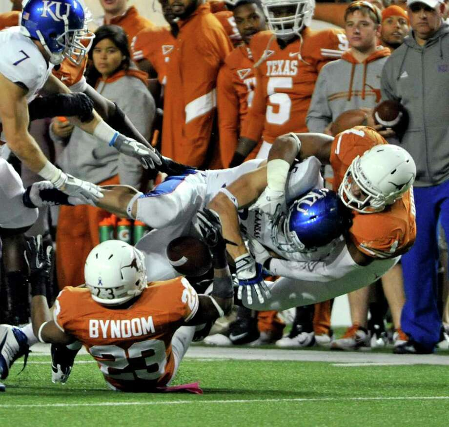 UT's Keenan Robinson (right) and Carrington Byndom force a fumble by Kansas' Brandon Bourbon in the second half. Photo: Michael Thomas/Associated Press