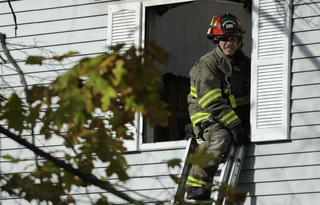 A Clifton Park Code firefighter exits the second floor of the apartment building in Twin Lakes, October 31, 2011,  that was destroyed by a fire over the weekend in Clifton Park, N.Y.  October 31, 2011.   (Skip Dickstein/Times Union) Photo: Skip Dickstein / NWest PRS 2011