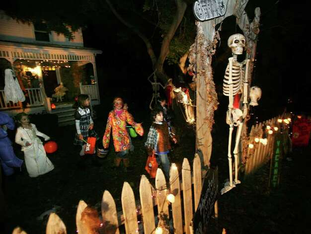 Halloween trick or treaters walk past a spooky skeleton after getting some candy at a home on Williams Road in Trumbull on Monday, October 31, 2011. Photo: Brian A. Pounds / Connecticut Post